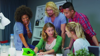 Cheerful creative business team working together with a computer tablet