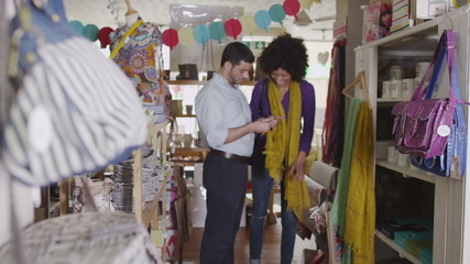 Happy attractive young couple shopping together in a small traditional gift shop