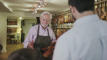 Father and son shopping together, looking at violins in a musical store