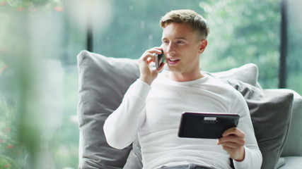 Attractive young man making a phone call with a computer tablet in his hand