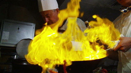 Professional chef in a restaurant kitchen cooking flambe style