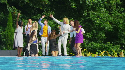 Glamorous attractive friends enjoying drinks and dancing by luxury pool