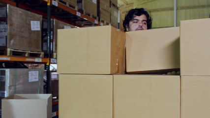Workers in high visibility clothing are stacking plain brown boxes onto a pallet