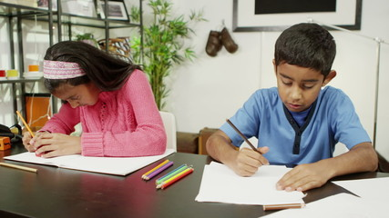 Brother and sister at home, writing and drawing with lots of colored pencils