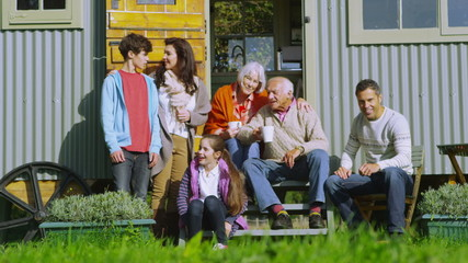 Portrait of happy extended family sitting outside caravan on an autumn day