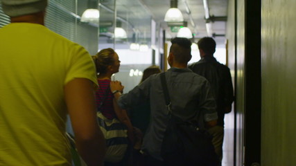 Young student group walking through the hallway in modern college building