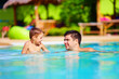 father and son having fun in outdoor pool, summer vacation