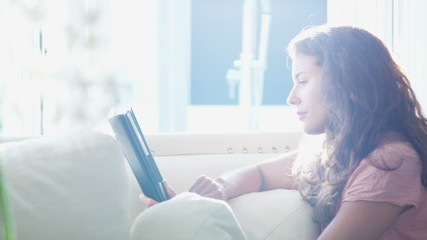 Attractive young woman using computer tablet sitting by the window
