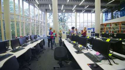 Diverse student group working together in a room full of computers.