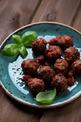 Meatballs with green basil leaves, close-up, selective focus