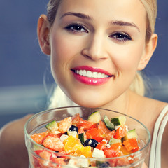 Smiling young woman eating salad