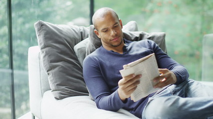 Attractive young man relaxing at home alone reading a newspaper