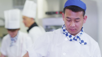 Head chef in commercial kitchen overseeing staff and offering advice