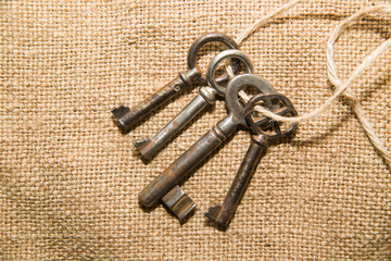 Four  very old keys tied with a rope on old cloth