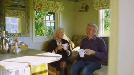 Cheerful mature couple relaxing inside quaint caravan in a natural setting