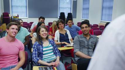 Cheerful students in a lecture are listening to their teacher