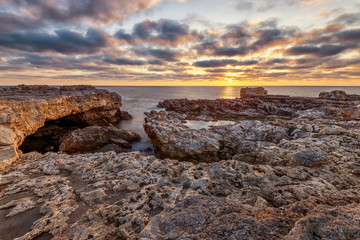 Beautiful dramatic sunrise on the rocky beach