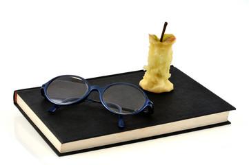 Un livre, des lunettes et un trognon de pomme