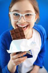 Kocham czekolade... Dziewczynka gryzie tabliczkę czekolady