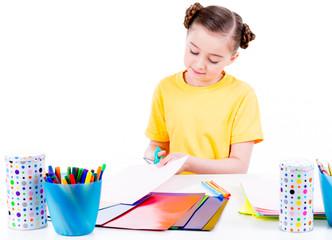 Cute little girl in yellow t-shirt cut scissor cardboard.