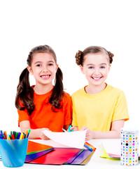 Cute little girls in colourful t-shirt cut scissor cardboard.