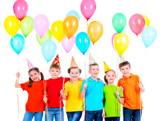 Group of children in colored t-shirts and party hats.