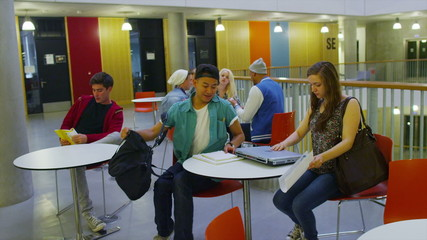 Cheerful diverse student group in large modern university building.