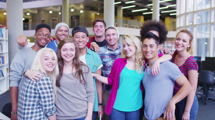Portrait of a happy mixed ethnicity group of student friends in college library.