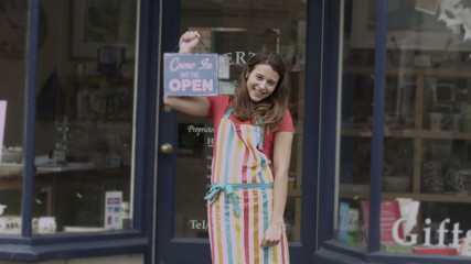Happy female shopkeeper holds up a sign to show she is open for business