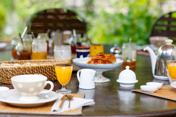 Table laid for breakfast outside with various jams coffee, crois