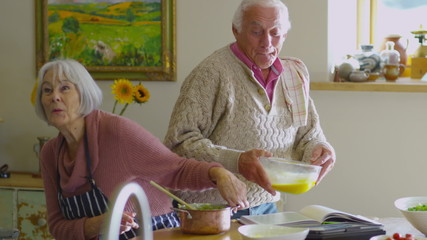 Happy young at heart senior couple preparing food together in kitchen at home