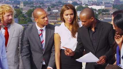 Attractive mixed ethnicity business team in open air meeting with city views