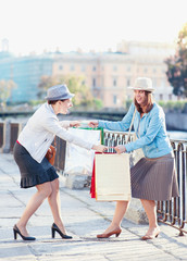 Two beautiful girls with shopping bags having fight in the city
