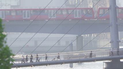View from a distance of morning commuters crossing a bridge over River Thames