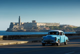 Old classic car on street of Havana with ocean and lighthouse in