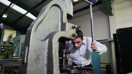 Young male machine operator working in a factory