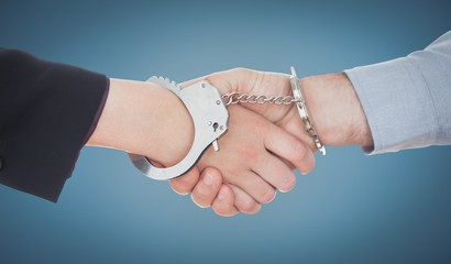 Composite image of business people in handcuffs shaking hands