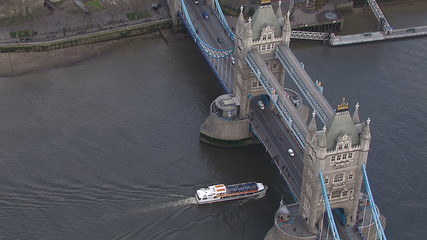 Aerial view of a boat passing underneath London's Tower Bridge
