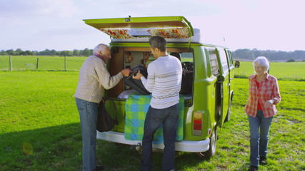 Happy affectionate family with camper van taking a holiday in the countryside