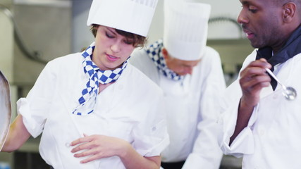 Chef cooking in commercial kitchen waits for head chef to taste & give approval
