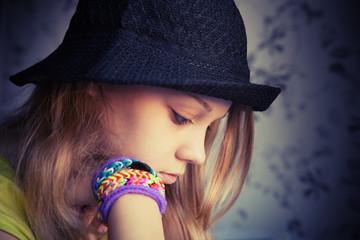 Profile portrait of beautiful blond teenage girl in black hat