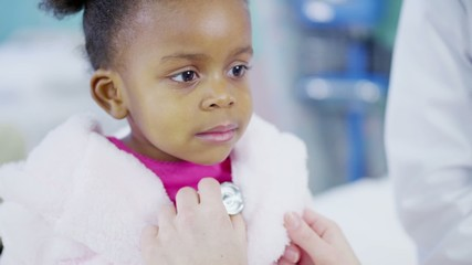 Female doctor uses a stethoscope to examine cute little girl in hospital.