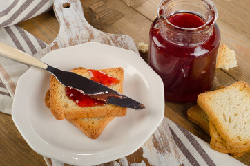 Strawberry jam topping a slice of toast on a white  plate.