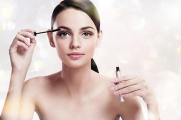 Charming young woman applying mascara