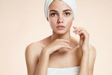 Scowling girl in shock of her acne with a towel on her head. poster