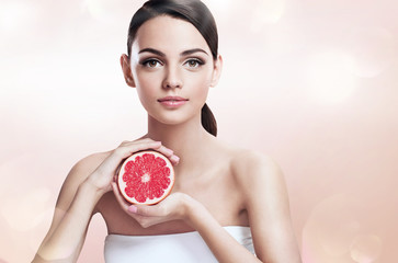 Young woman with grapefruit cut in half