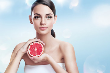 Young lady with grapefruit cut in half, healthy life concept