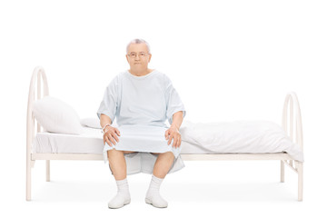 Mature patient in a hospital gown sitting on a bed