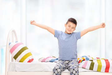 Sleepy little boy in pajamas stretching himself