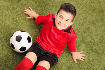 Junior soccer player sitting on a green field